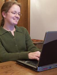 Professional woman working at laptop - Custom .NET software from Tech Info Systems
